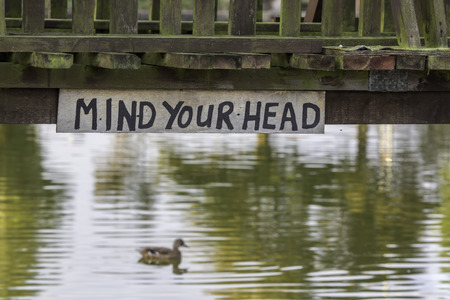 keep your hands: Mind Your Head. A quirky hand-written sign displayed below a low river bridge.