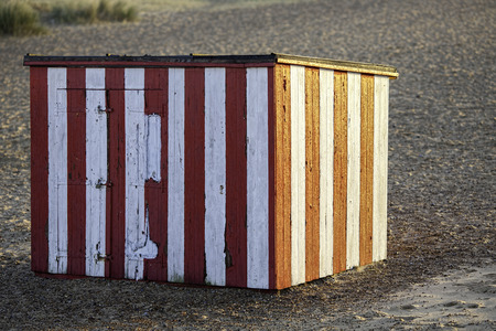 weatherworn: A single weather-worn red and white striped beach hut. Pictured at sunrise.