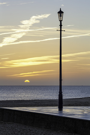 renewed: The new light of dawn on the horizon pictured with an old victorian lamp on the English coast. The perpetually renewed light of the sun contrasts with the extinguished old world gas lamp.