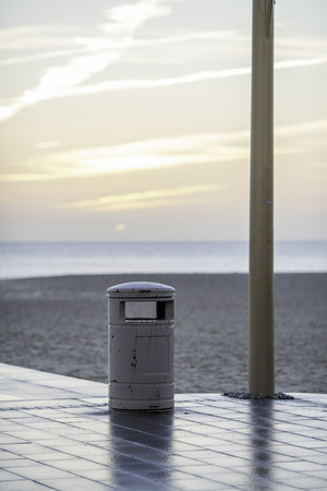 cleanup: Empty trash can by a lamp post at sunrise. Beach clean-up. Stock Photo