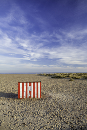 Quirky red striped beach hut. A fun travel vacation image signifying a secluded vacation getaway. Great postcard image with natural copy space. Stock Photo