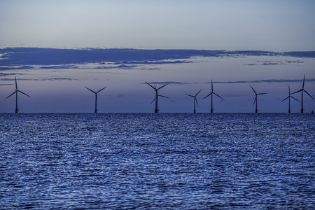 Offshore wind farm on the horizon, Wind turbines caught in a blue pre-dawn glow giving the image a cool serene look, Effortless silent energy production and conservation throughout the night.