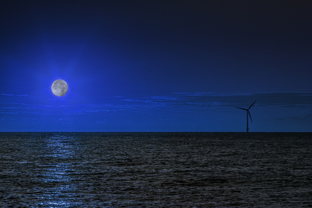 constancy: A solitary wind turbine on the sea horizon at night with the water bathed in moonlight. This composite image emphasisies the peaceful constancy  of renewable energy production. Stock Photo