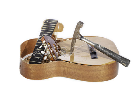 An acoustic guitar that has been demolished with a hammer by its frustrated guitarist owner. No more musical instrument practice. Stock Photo