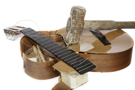 An acoustic guitar that has been smashed with a lump hammer by its frustrated guitarist owner. No more music practice.