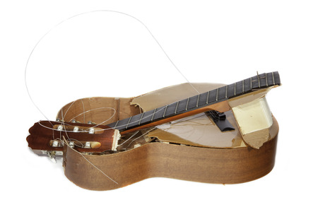 snapped: An acoustic guitar that has been smashed with a lump hammer by its frustrated guitarist owner. No more practice.