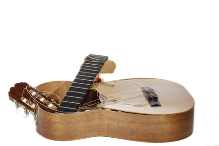 snapped: An broken classical acoustic guitar left in bits and pieces by its disillusioned musician owner, Now a really rubbish guitar. White background with copy space.