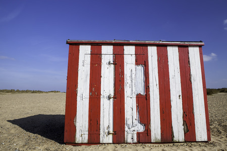 run down: A red and white striped beach hut with flaky paint representing budget vacation property. A holiday home in need of renovation. Stock Photo