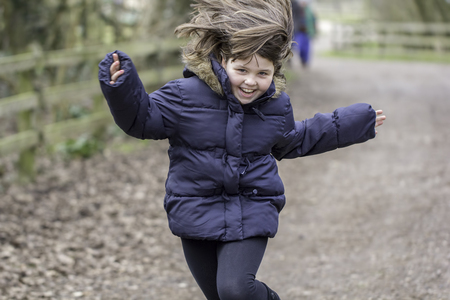 beaming: A young happy caucasian girl with brown hair, aged around nine years old, is running along a wide country path or lane towards the camera. She is in a blue warm coat, is animated and smiling.