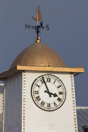 britannia: Classic white clock tower with gold Britannia  weather vane Stock Photo