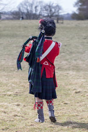 Scots guards piper from a war reenactment group on the battlefield with bagpipes. In reproduction traditional uniform. Stock Photo