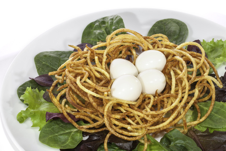 spiralized: Slimmers low calorie boiled quail egg salad made with spiralizer. Nest of fried spiralized potato making crispy french fries.