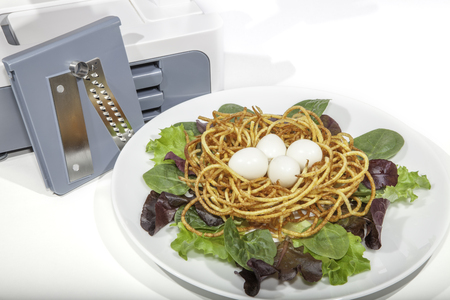 spiralized: Vegetable spiralizer with healthy organic spiralized meal. Boiled quail eggs in potato nest with baby leaf salad.
