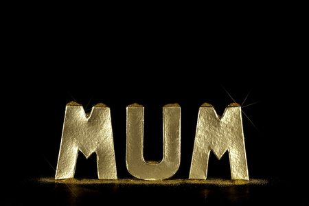 Golden Mum Text. Letters spelling MUM in simulated gold bullion with gold dust. For a special mum worth her weight in gold. Black background with copy space. Stock Photo