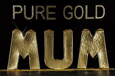 Pure Gold Mum word. Precious and golden. Special mothers day or birthday card image with the word mum in sparkling gold letters. Beautiful contrast wording against black background. Stock Photo
