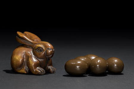 Easter bunny rabbit netsuke with mini Easter eggs. Carved wooden rabbit netsuke looking very much like the Easter bunny next to some mini chocolate truffle Easter eggs Stock Photo