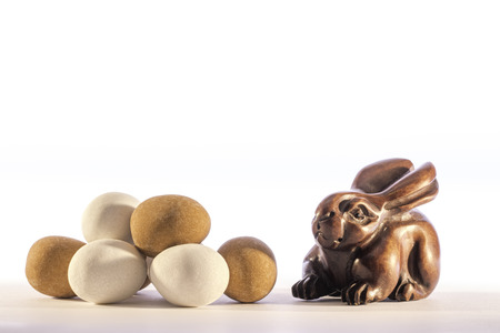 Traditional carved netsuke rabbit representing the Easter bunny alongside a pile of mini Easter eggs. White background with copy space.