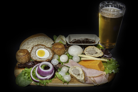 Ploughmans pub lunch including scotch egg; pork pies, ham; pickled onions and cheese served with a pint of lager beer. Isolated against a black background.