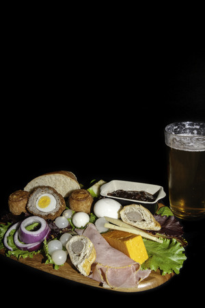 Traditional English pub meal of a ploughmans lunch served with a pint of lager. The typical cold food includes pork pies, ham, hard boiled eggs and cheese with salad. Isolated against a black background with copy space. Stock Photo