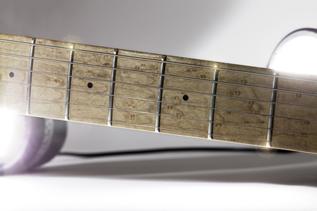 Electric guitar neck. Maple fingerboard under studio lighting with lens flare.