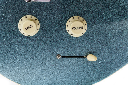 Vibrant sound. Volume and tone controls with pickup selector switch on blue glitter finish glam rock electric guitar.