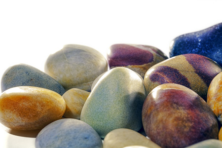Colourful assortment of smooth tumbled beach pebbles studio shot against white background with copy space. The stones have been tumble polished to a satin shine. Stock Photo