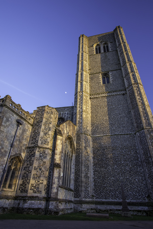 monastic: Wymondham abbey, an ancient Norman church in East Anglia UK. Here the impressive stone-clad tower is pictured during evening sunset. Stock Photo