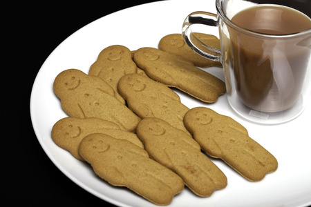 Afternoon snack comfort food. Gingerbread men biscuits and a cup of tea. Small ginger biscuits and tea in a see through mug on a white plate against a black background. Stock Photo