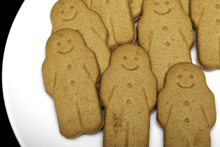 A plate of gingerbread men ginger biscuits . Afternoon snack comfort food.