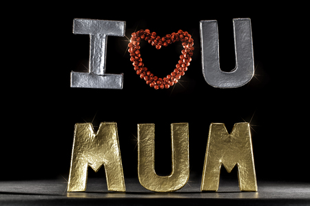 I Love You Mum. Silver and Gold letters and words with red heart. Mother's day or birthday occasion image against black background.