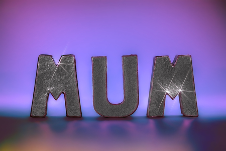 Mum word in glamorous sparkling silver foil letters with pink lights providing background and reflection. Feminine with seventies party style glam. Ideal birthday, mother's day and party occassion image.