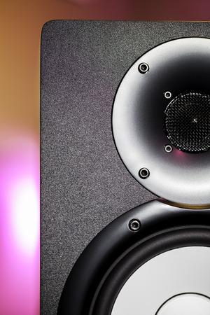 DJ studio monitor speaker with disco lighting background. Nightclub party sound system equipment.