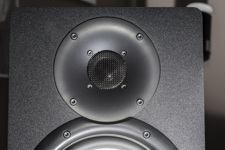 Black hi-fi speaker dome tweeter for high frequency sound. The treble component driver of a black loudspeaker in close up.  Stock Photo