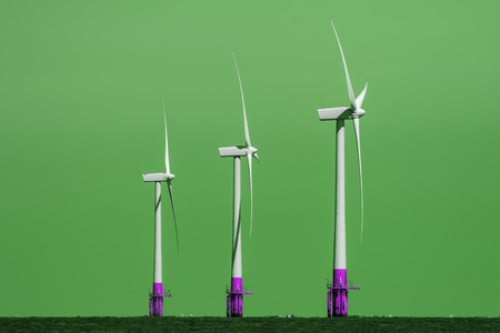Green Energy Production. Three offshore wind turbines in profile against color manipulated background. Stock Photo