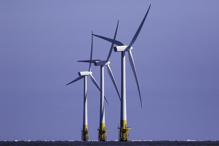 Group of three offshore wind farm turbines providing clean renewable energy. Crossed blades and ascending in height providing an aesthetic geometric pattern against a blue sky background. Stock Photo