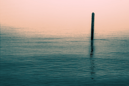 Calm water with solitary wooden post and reflection. Simple serene image with connotations of Zen Buddhism. Stock Photo