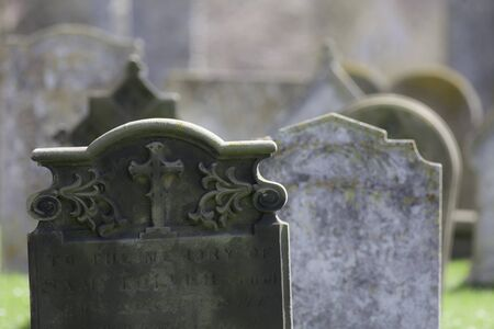 Ancestry. Ghostly graveyard headstones. Hazy selective focus image of an ancient English cemetery. Stock Photo