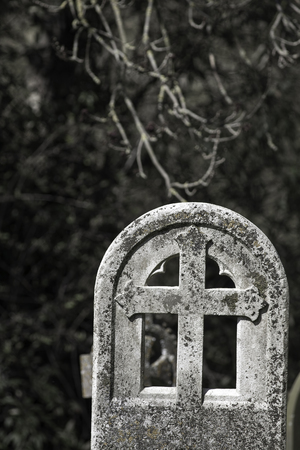 Remembrance and Mortality. Ancient graveyard headstone with Christian cross. From an English churchyard.
