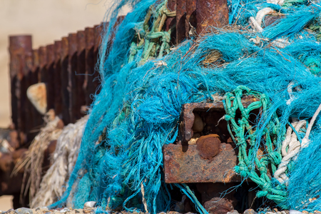 Dangerous plastic sea pollution. Tangled nylon fishing net washed up and caught on a rusty beach groyne. Stock Photo
