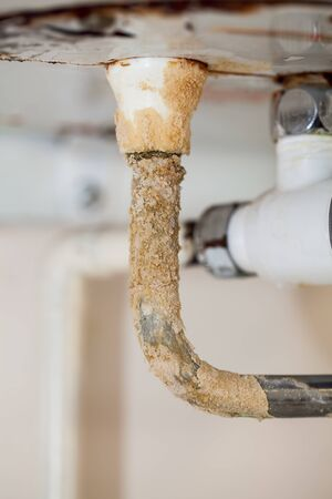 Heavy limescale deposit on a rusty hot water system pipe. Bad plumbing problem cause by hard water leaking. Stock Photo