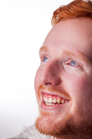 Happy ginger haired young man. Smiling face of lad with red hair and skin complexion, isolated against white background with copy space. Stock Photo