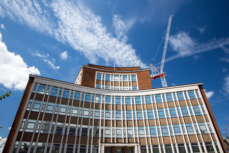 recently: Modern curved office building with construction crane against blue sky.