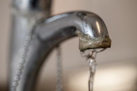 Tap limescale. Selective focus on the hard water deposit of a running kitchen or bathroom faucet.