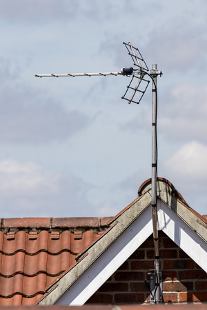 TV aerial on tiled roof top. Metal antenna on residential building. Television reception equipment.