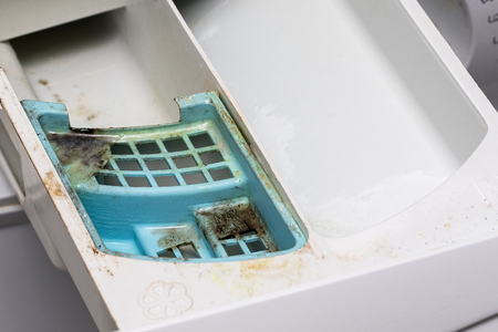 Dirty mouldy washing machine detergent and fabric conditioner dispenser drawer. Mold and dirt in washing machine. Stockfoto