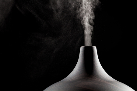 사용중인 초음파 아로마 오일 디퓨저의 닫습니다. 원자화 된 물방울이 공기 중에 분배됩니다.
