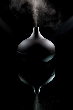 air diffuser: Complimentary therapy and alternative medicine. Modern aromatherapy aroma diffuser working. Dark moody image backlit with spotlights against black background. Modern design image also reflecting questions on whether alternative medicine has a sinister sid