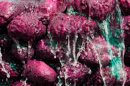 mundo contaminado: Contaminación química. Agua dulce corriendo rocas rojas de color artificial. Resumen de la imagen de fondo que representa el daño ambiental de contaminación de productos sintéticos en el agua potable. Foto de archivo