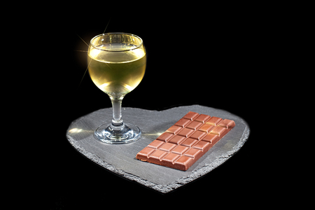 Love wine and chocolate. Luxury evening in with alchohol. Glass of white wine and bar of chocolate on slate heart platter. Isolated against black background with copy space. Stock Photo