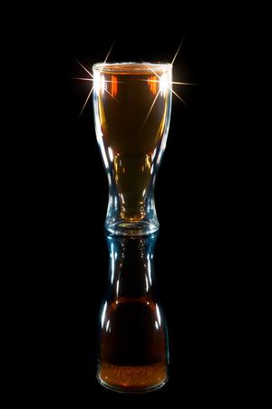 国際ビールの日。ボトルの形をしたガラスのラガーのパイント。ビール賞を受賞。コピー スペースで黒背景にソフトなキラキラ画像。